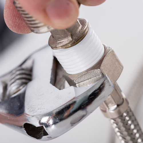 A Local Plumber Tightens a Hose Connector